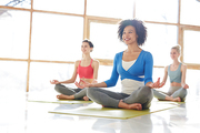 Happy female and her friends sitting on mats in pose of lotus and looking at their yoga instructor