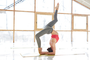 Young flexible woman doing head stand and stretching her legs during yoga training in gym