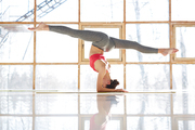 Active girl performing twine in the air while standing on head during yoga training in fitness center