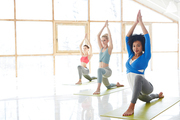 Young sporty women exercising on mats in modern fitness center or gym