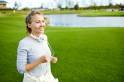 Happy active girl in sportswear running along riverside in rural environment on summer morning