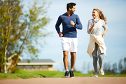 Amorous young couple in activewear running in rural environment on sunny day
