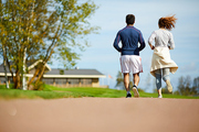 Back view of young active couple jogging in rural environment on summer morning