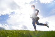 Active young woman jogging at skyline against sunshine on cloudy sky in natural environment
