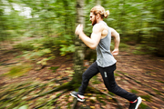 Young sportsman moving forwards while running in the forest with blurry trees around him
