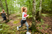 Young active female and her boyfriend running in birch tree forest around blurry green foliage in the morning