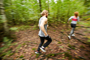 Active young man running after his girlfriend while moving down forest path among blurry birch trees