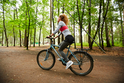 Active girl in sportswear sitting on bicycle while moving down forest road on summer day or weekend