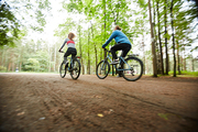 Rear view of young active cyclists on their bicycles riding along road in natural environment on summer weekend
