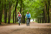 Young active man and woman sitting on bicycles while moving along road in park and talking to one another