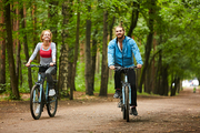Happy guy and his girlfriend on bicycles looking at you while riding down forest road or in park