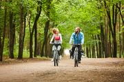 Young man and woman in activewear talking while cycling on road in park on summer weekend