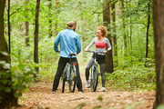 Active girl and guy with bicycles standing on forest path and discussing what way to choose for ride