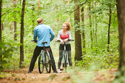 Young female cyclist in activewear talking to her boyfriend during chill in the forest on summer day