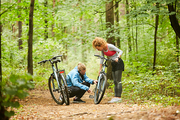 Young cyclist checking bicycle chain of active girl on forest path and explaining what can be done about it