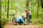 Young woman standing by her bicycle turned upside down and taking to her boyfriend repairing chain or wheel
