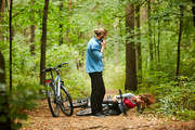 Young female cyclist with broken leg lying on forest path while her boyfriend calling for help on smartphone