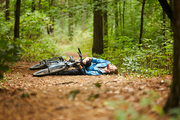 Active young man holding by his hurt or broken leg while lying on forest path by his bicycle
