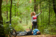 Young female cyclist with smartphone trying to catch signal in the forest while standing on path by her boyfriend with broken leg lying on the ground