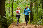 Young sporty couple running down forest path or in park in the morning between green trees