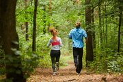 Back view of young sportsman and sportswoman having running workout in the forest among trees