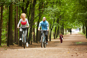 Two young active cyclists riding on bicycles along wide road between trees in park on summer day