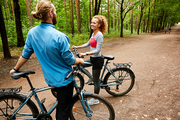 Happy young active couple with bicycles having talk while standing on forest road on summer deay