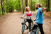 Young active man explaining how to get out of forest to pretty sportswoman cycling on road