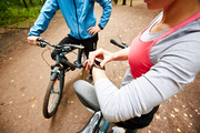 Young female cyclist checking time in smartwatch while deciding where to go cycling with boyfriend