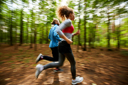 Young couple in activewear running on forest road with blurry trees on background