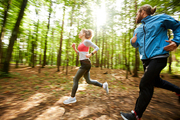 Young active man and his girlfriend jogging out in the forest on sunny day among blurred trees