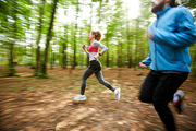 Morning training of active young couple jogging in the forest on summer day among blurry trees