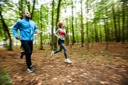 Young man in activewear and his girlfriend running together in the forest during morning chill