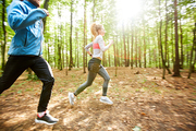 Young couple in activewear moving on the ground in the forest on sunny morning on background of blurry trees