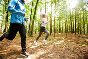 Active guy and girl in sportswear running down forest road while training in the morning