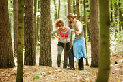 Young sportsman helping his girlfriend with hurting leg to walk in the forest after unlucky training