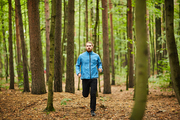 Young sportsman running among pines and birch trees along forest path while training in the morning
