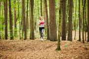 Young sportswoman running down forest path among trees while training on summer morning