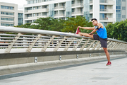 Full-length portrait of confident young athlete doing warm-up exercises before jogging in park