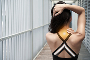 Rear view of woman suffering from stiff neck
