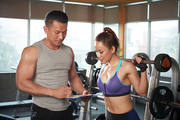 Personal trainer explaining program of training to pretty woman