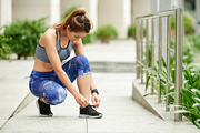 Young sportswoman tying shoe laces before running