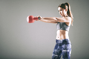 Pretty sportswoman doing exercises with heavy kettlebell, isolated on grey