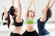 Three pretty Asian women doing stretching exercise while sitting on floor in spacious dance hall