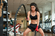 Asian young woman concentrated on battle rope exercise