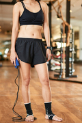 Fit woman with skipping rope standing in gym