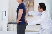 Vietnamese sports doctor examining spine of young patient