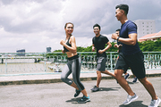 Young cheerful people running behind pretty fit woman