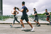 Asian young people running on the bridge together