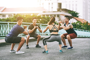 Group of Asian young people doing squats outdoors